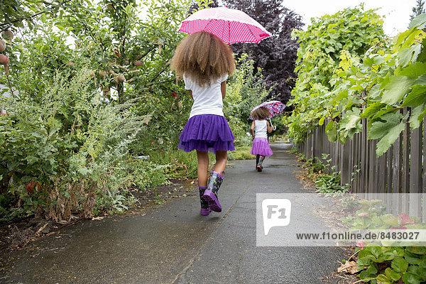 Mixed race girls carrying umbrellas outdoors