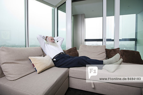 Full length of senior man relaxing on sofa with hands behind head at home