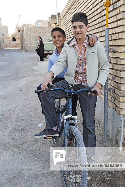 Boys with a bicycle in a residential alleyway  Na'in  Isfahan Province  Iran