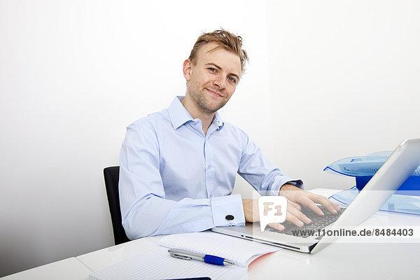 benutzen  Portrait  Schreibtisch  Fröhlichkeit  Notebook  Geschäftsmann  Büro