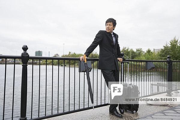 angelehnt  Geschäftsmann  Gepäck  Fluss  vorwärts  Länge  Geländer  voll