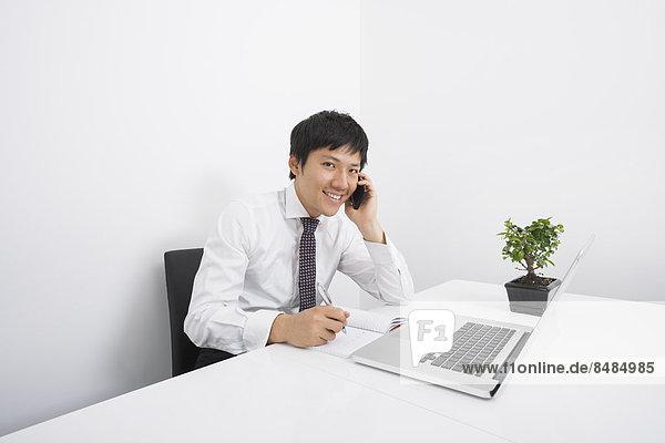 benutzen  Portrait  Schreibtisch  Fröhlichkeit  Geschäftsmann  arbeiten  Telefon  Büro  Handy