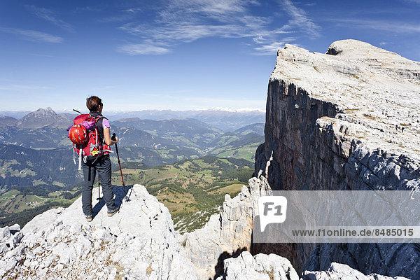 Bergsteigerin auf der Kreuzkofelscharte beim Aufstieg auf den Heiligkreuzkofel ¸ber den Heiligkreuzkofelsteig in der Fanesgruppe im Naturpark Fanes-Sennes-Prags  hinten der Heiligkreuzkofel  unten das Gadertal  Dolomiten  S¸dtirol  Italien