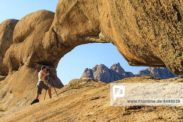 Fotograf an einem Felsenbogen  Damaraland  Namibia