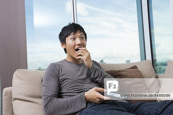 Interior  zu Hause  Mann  sehen  Couch  Überraschung  Fernsehen  Erwachsener Mittleren Alters  Erwachsene Mittleren Alters