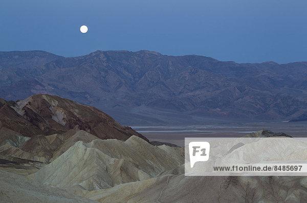 Vollmond ¸ber der Bergkette Panamint Range und dem Death Valley in der Morgend‰mmerung  vom Zabriskie Point  vorne Erosionsstrukten im Gestein  Badlands von Gower Gulch  Death-Valley-Nationalpark  Kalifornien  USA