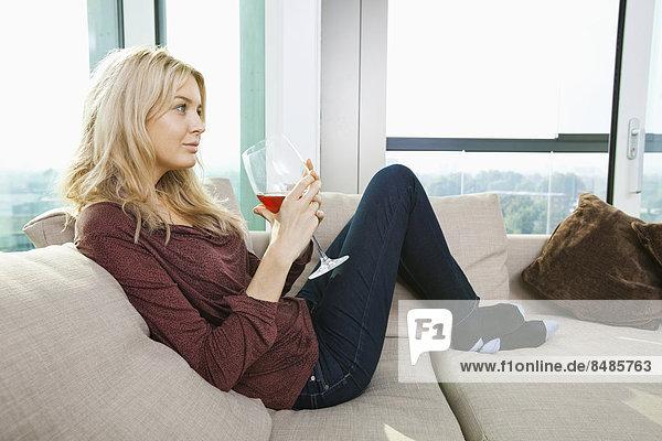 Interior  zu Hause  Frau  Glas  Wein  Zimmer  Ansicht  jung  Seitenansicht  Wohnzimmer