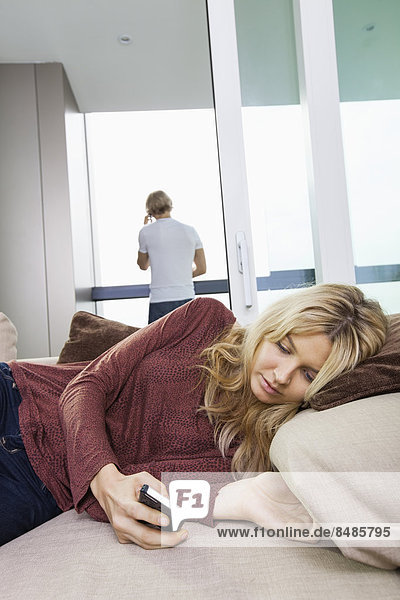 Young woman text messaging while rear view of man using cell phone in background at home