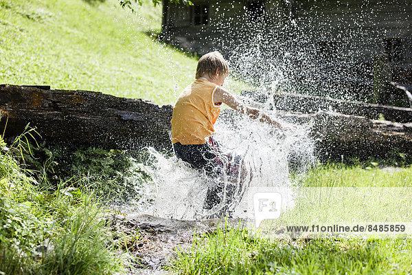Junge springt in einen Bach  Tirol  ÷sterreich Junge springt in einen Bach, Tirol, ÷sterreich