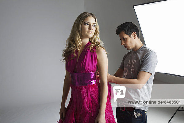 Designer adjusting dress back on fashion model in studio