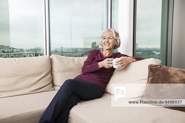 Interior  zu Hause  Senior  Senioren  Frau  Entspannung  Couch  Becher  lächeln  Kaffee