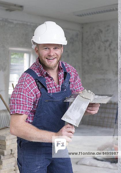 Handwerker auf Baustelle mit Kelle
