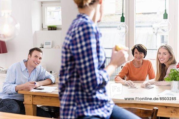 Mutter mit erwachsenen Kindern am Tisch  junge Frau im Vordergrund