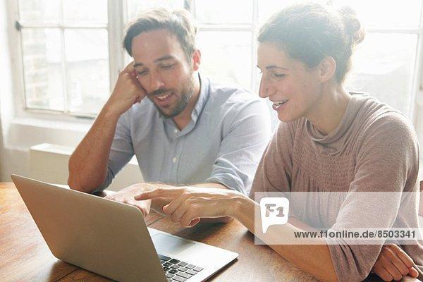 Mittleres erwachsenes Paar mit Laptop