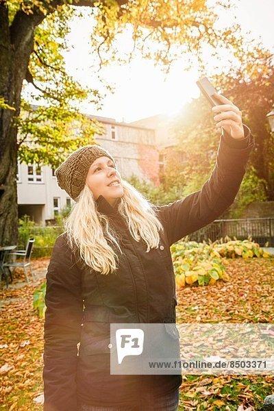 Junge Frau fotografiert sich im Garten