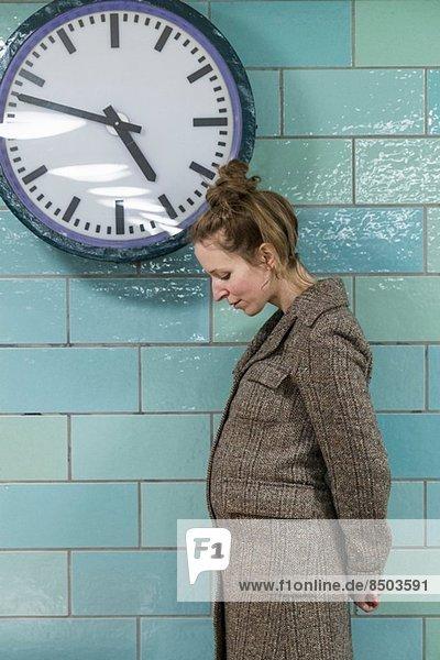 Schwangere Frau nach der Uhr