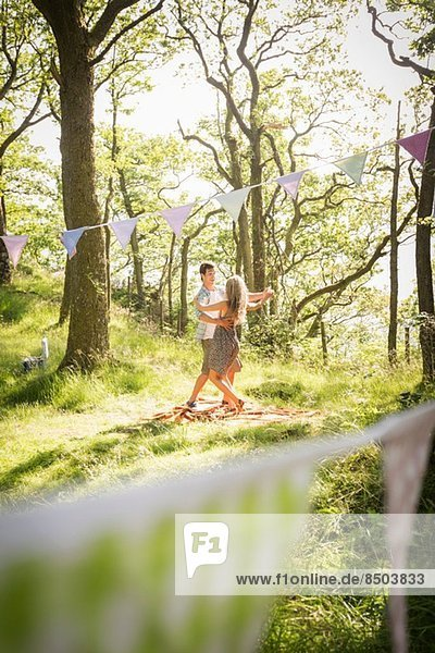 Young couple dancing in forest