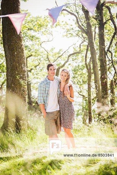 Porträt eines jungen Paares im Wald stehend