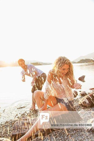 Young couple by lake  man splashing woman  Cumbria  England  UK