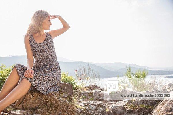 Young woman sitting on rocks shielding eyes