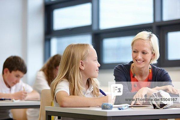 Lehrerin bei der Arbeit mit Schülerin im Klassenzimmer