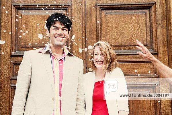 Neuvermähltes Ehepaar in der Konfetti-Dusche