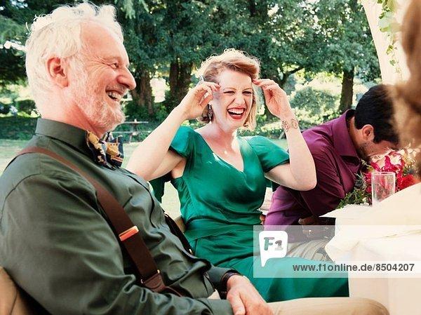 Neuvermähltes Ehepaar mit lachenden Eltern bei der Hochzeitsfeier