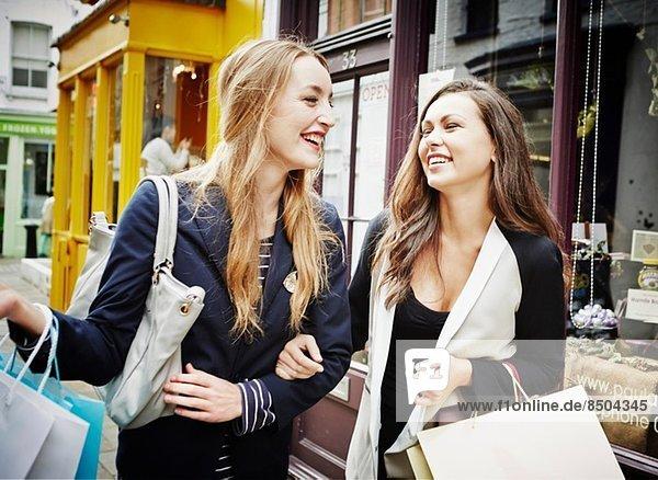 Junge Frauen  die mit Einkaufstaschen und Lachen die Straße hinuntergehen.