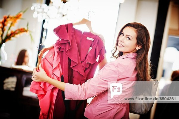 Young woman looking pink top on hanger