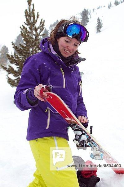 Frau beim Anziehen der Skier
