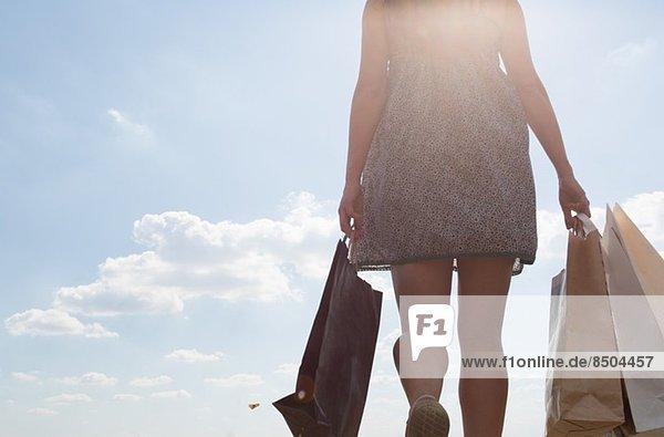 Mittelteil der Frau mit Einkaufstaschen Mittelteil der Frau mit Einkaufstaschen