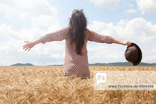 Mittlere erwachsene Frau im Weizenfeld stehend mit breiten Armen Mittlere erwachsene Frau im Weizenfeld stehend mit breiten Armen