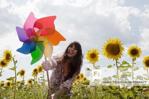 Frau hält Windmühle im Sonnenblumenfeld Frau hält Windmühle im Sonnenblumenfeld