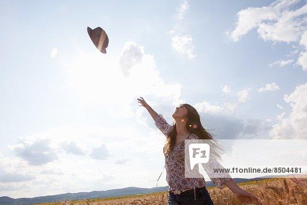 Mittlere erwachsene Frau  die einen Hut in die Luft wirft. Mittlere erwachsene Frau, die einen Hut in die Luft wirft.