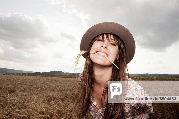 Mittlere erwachsene Frau mit Weizen im Mund