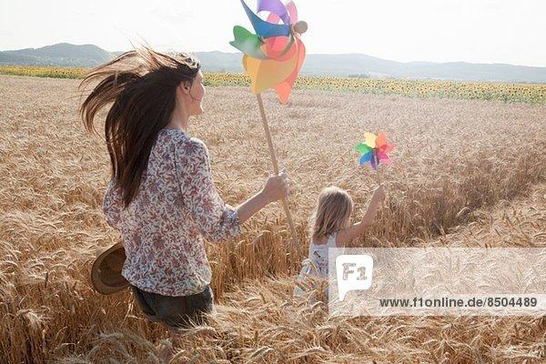 Mutter und Tochter laufen durchs Weizenfeld Mutter und Tochter laufen durchs Weizenfeld