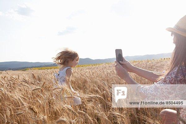 Mutter fotografiert Mädchen  die durchs Weizenfeld läuft Mutter fotografiert Mädchen, die durchs Weizenfeld läuft