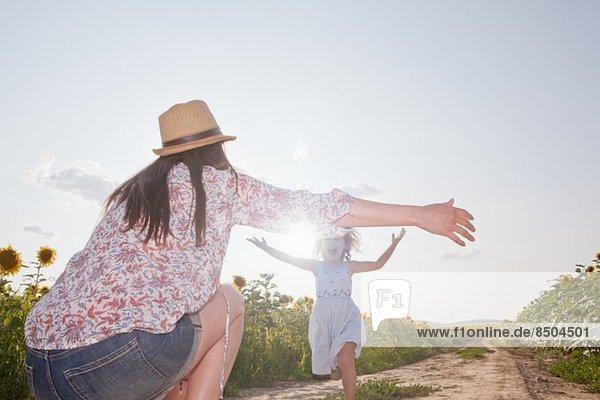 Mädchen läuft mit offenen Armen durchs Feld zur Mutter Mädchen läuft mit offenen Armen durchs Feld zur Mutter