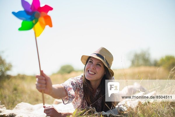 Frau auf der Vorderseite liegend  Windmühle haltend Frau auf der Vorderseite liegend, Windmühle haltend
