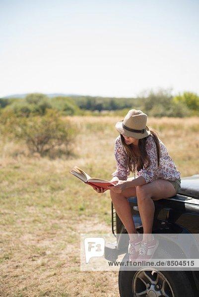Mittlere erwachsene Frauen  die auf der Motorhaube des Autos sitzen und Buch lesen Mittlere erwachsene Frauen, die auf der Motorhaube des Autos sitzen und Buch lesen