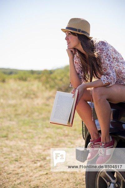 Mittlere erwachsene Frauen sitzen auf der Motorhaube des Autos und halten Buch mit Kinn an der Hand. Mittlere erwachsene Frauen sitzen auf der Motorhaube des Autos und halten Buch mit Kinn an der Hand.