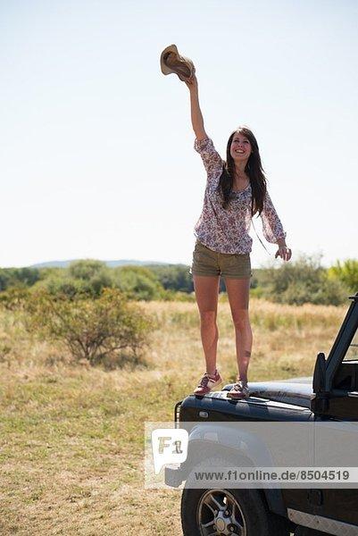 Mittlere erwachsene Frauen  die auf der Motorhaube des Autos stehen und den Hut schwenken. Mittlere erwachsene Frauen, die auf der Motorhaube des Autos stehen und den Hut schwenken.