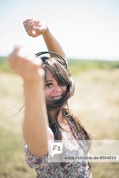 Porträt einer mittleren erwachsenen Frau  die mit erhobenen Armen und Kopfhörern im Feld tanzt. Porträt einer mittleren erwachsenen Frau, die mit erhobenen Armen und Kopfhörern im Feld tanzt.