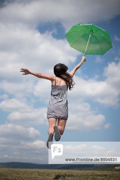 Mittlere erwachsene Frau mit grünem Regenschirm  springend Mittlere erwachsene Frau mit grünem Regenschirm, springend