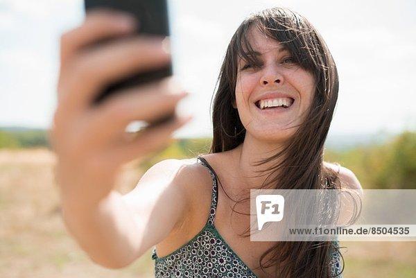 Mittlere erwachsene Frau beim Fotografieren von Selbstporträts Mittlere erwachsene Frau beim Fotografieren von Selbstporträts