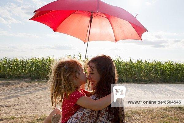 Mutter und Tochter umarmen sich unter rotem Regenschirm