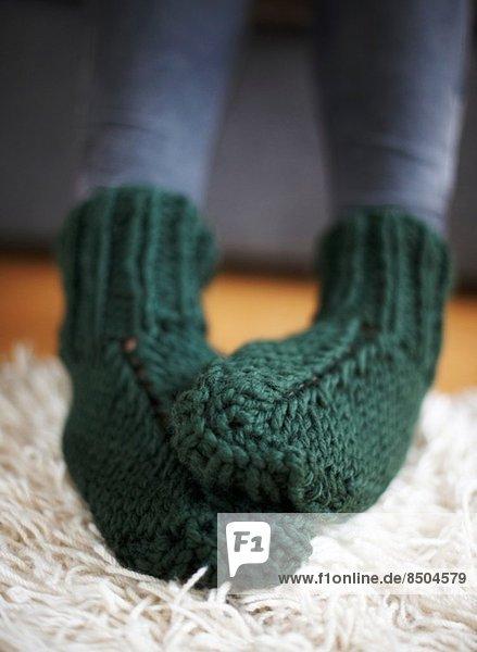 Paar Füße in grün gestrickten Socken