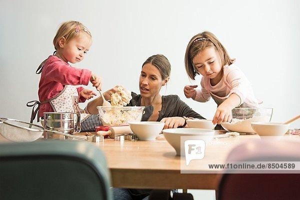 Mutter und Kinder backen  Teig mischen