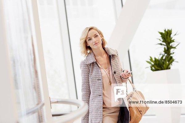 Mittlere erwachsene Frau mit Trolley-Koffer bei der Ankunft am Stadtflughafen