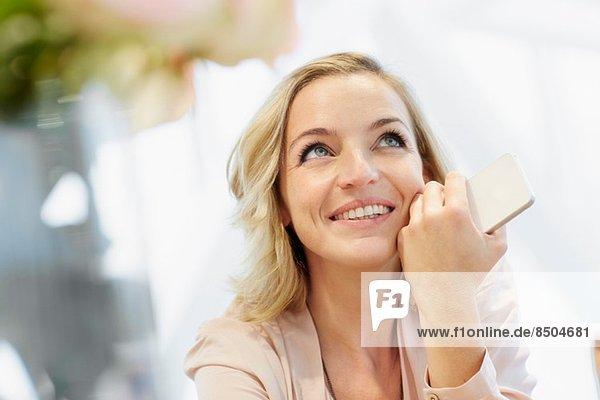 Porträt einer mittleren erwachsenen Frau mit mobilem Tagträumen